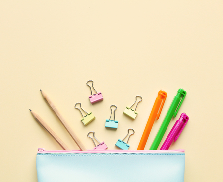Flat lay composition of pastel blue pencil case with pens, pencils,paper binders.Copy space,beige background.Top view on various stationery on desk. Creative workspace background.Back to school concept. Standard-Bild