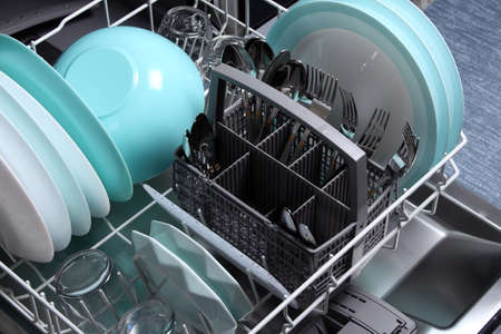 Open dishwasher with clean utensils in it,close up.Clean plates,glasses,forks,spoons after washing in the dishwasher.Dishwasher machine after cleaning process.