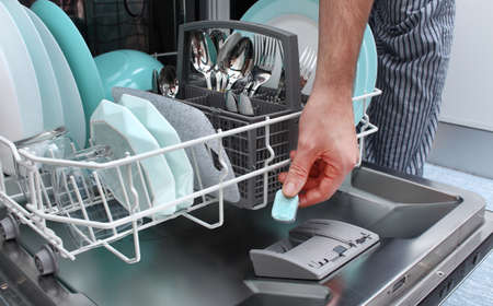Loading the tablet into the dishwasher. A man puts the tablet in the dishwasher to wash dirty dishes.