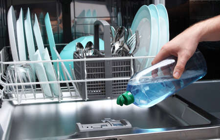 Loading the gloss liquid into the dishwasher. Man filling dishwasher with gloss liquid.