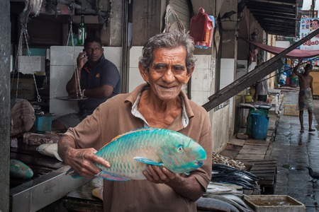 parrotfish: Galle, Sri Lanka, 28 May 2016. The seller offers to buy the big blue fish to passersby.