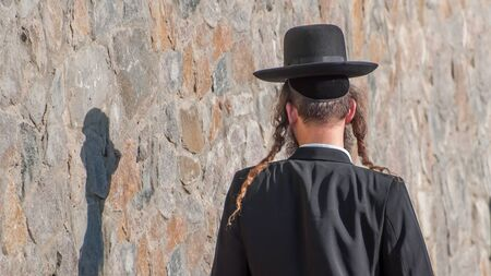 Jew Hasid ethnic headdress. Human shadow on stone wall. Banque d'images