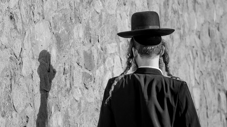 hasidism: Jew Hasid ethnic headdress. Human shadow on stone wall. Stock Photo