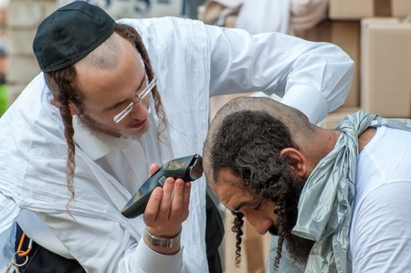 hasid: A young Hasid hairdresser mows the street another Hasid. Uman, Ukraine - October 2, 2016: Every year, thousands of Orthodox Bratslav Hasidic Jews from different countries gather in Uman to mark Rosh Hashanah, Jewish New Year, near the tomb of Rabbi Nachma