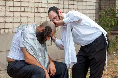 hasidism: A young Hasid hairdresser mows the street another Hasid. Uman, Ukraine - October 2, 2016: Every year, thousands of Orthodox Bratslav Hasidic Jews from different countries gather in Uman to mark Rosh Hashanah, Jewish New Year, near the tomb of Rabbi Nachma