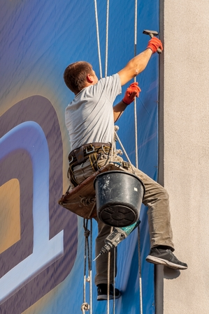 wall mounted: Climber on a vertical wall mounted billboard. Stock Photo