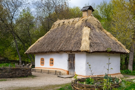 National Museum Pirogovo in the outdoors near Kiev. Ancient peasant Ukrainian house in the spring with a thatched roof in the old village of national architecture, Ukraine.