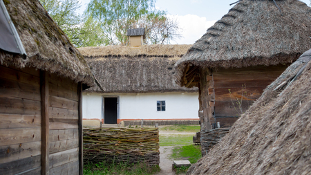 National Museum Pirogovo in the outdoors near Kiev. Ancient peasant Ukrainian house in the spring with a thatched roof in the old village of national architecture, Ukraine. Wooden and clay cottage. Editorial