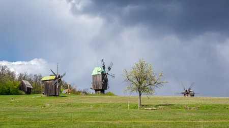National Museum Pirogovo in the outdoors near Kiev. Ancient traditional wooden windmill, spring landscape. National architecture.