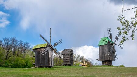 National Museum Pirogovo in the outdoors near Kiev. Ancient traditional wooden windmill, beautiful spring landscape with sky. National architecture.