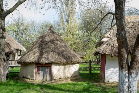 National Museum Pirogovo in the outdoors near Kiev. Ancient peasant Ukrainian old building with a thatched roof, spring landscape in the old village of national architecture, Ukraine.