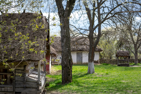 National Museum Pirogovo in the outdoors near Kiev. Old rural courtyard with an antique wooden well and wooden building, spring landscape. Peasant house.