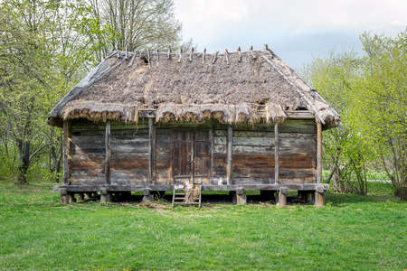 National Museum Pirogovo in the outdoors near Kiev. Ancient rural Ukrainian old wooden building with a thatched roof, spring landscape in the old village of national architecture, Ukraine.