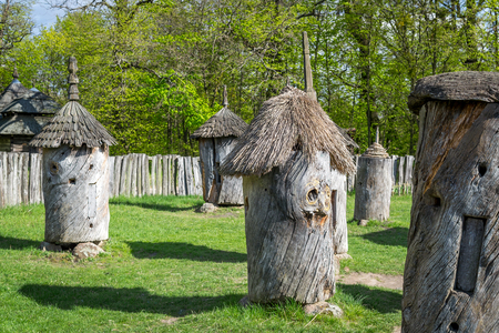 National Museum Pirogovo in the outdoors near Kiev. Ancient apiary. Old wooden hives on the meadow in the countryside.