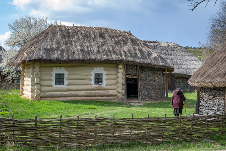 campesino: National Museum Pirogovo in the outdoors near Kiev. Ancient peasant Ukrainian house with a thatched roof, spring landscape in the old village of national architecture, Ukraine.