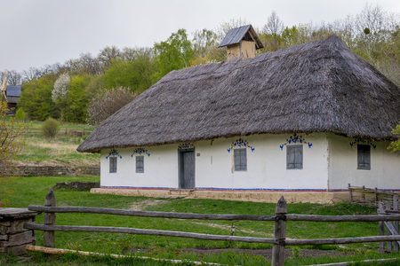 National Museum Pirogovo in the outdoors near Kiev. Ancient peasant Ukrainian house with a thatched roof, spring landscape in the old village of national architecture, Ukraine.