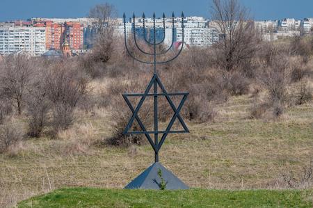 Menorah jest symbolem judaizmu, narodowo-religijnego znaku Izraela. Sześciopunktowa gwiazda Dawida. Pomnik ofiar holokaustu we wsi Bogdanovka. Ukraina. Publikacyjne