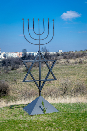 The menorah is a symbol of Judaism, the national-religious sign of Israel. The six-pointed star of David. Monument to the victims of the Holocaust in the village of Bogdanovka. Editorial
