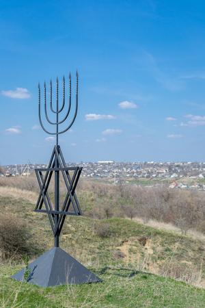 Menorah jest symbolem judaizmu, narodowo-religijnego znaku Izraela. Sześciopunktowa gwiazda Dawida. Pomnik ofiar holokaustu we wsi Bogdanovka. Ukraina.