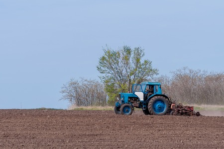 An old tractor in the field plows the land. Spring landscape of a countryside, a farm. Stok Fotoğraf