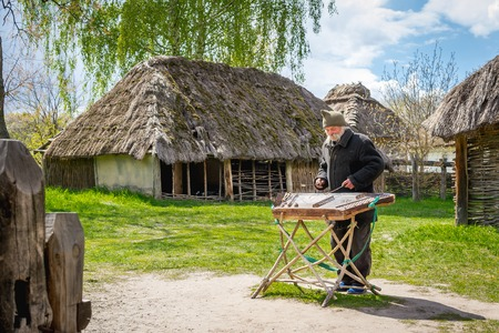 Kyiv, Ukraine - April 23, 2017: An elderly Ukrainian man, a peasant with a long mustache and beard, plays an ancient musical instrument of cymbals. Vintage village with wooden houses. Museum Pyrohiv