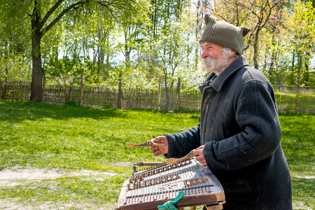 Kyiv, Ukraine - April 23, 2017: An elderly Ukrainian man, a peasant with a long mustache and beard plays an ancient musical instrument of cymbals. Spring landscape. Old Street Musician. Museum Pyrohiv