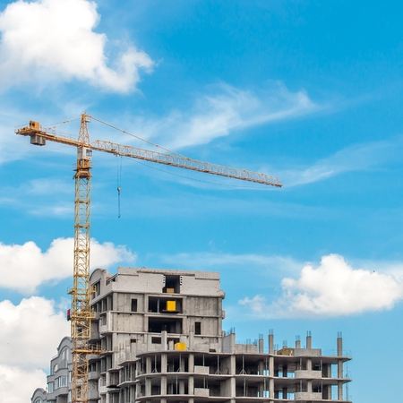 A large construction crane against the blue sky.