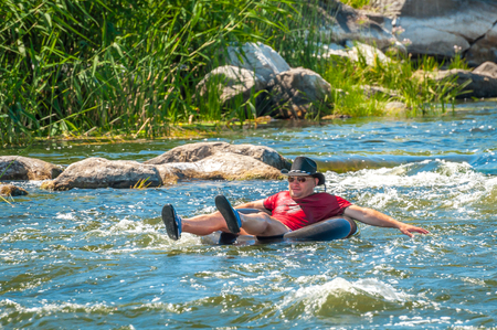 Village Myhiya, Nikolaev region, Ukraine - July 2, 2017: A gentleman in a black hat rafting on a river on a rubber inflatable wheel. A popular place for extreme recreation. Editorial