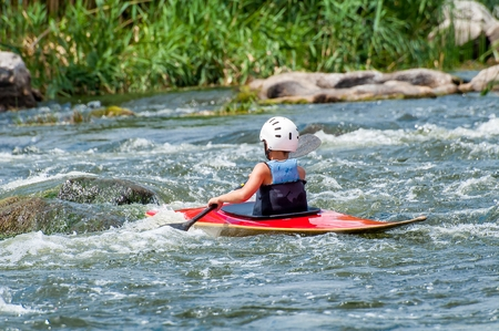 A teenager trains in the art of kayaking. Boat boats on rough river rapids. The child is skillfully engaged in rafting.