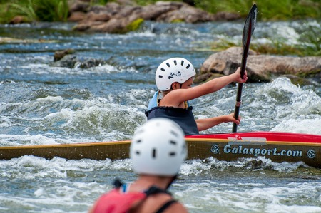 The village of Mihia, Ukraine - July 9, 2017. A teenager trains in the art of kayaking. Boat boats on untreated river rapids. The child skillfully engaged in rafting under the control of parents. Éditoriale