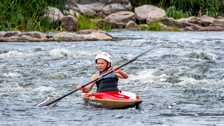 Village Myhia, Mykolayiv region, South Bug River, Ukraine - July 9, 2017: A teenager trains in the art of kayaking. Boat boats on rough river rapids. The child is skillfully engaged in rafting.