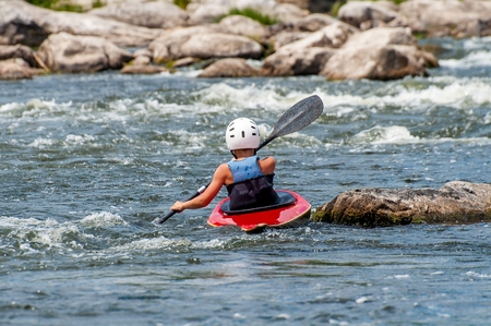 paddles: A teenager trains in the art of kayaking. Slalom boats on rough river rapids. The child is skillfully engaged in rafting.
