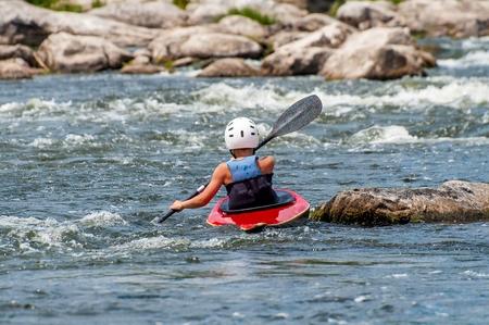 Nastolatek trenuje w sztuce kajakarstwa. Slalomowe łodzie na wzburzonych rzecznych rzecznych progach. Dziecko jest umiejętnie zaangażowane w rafting.