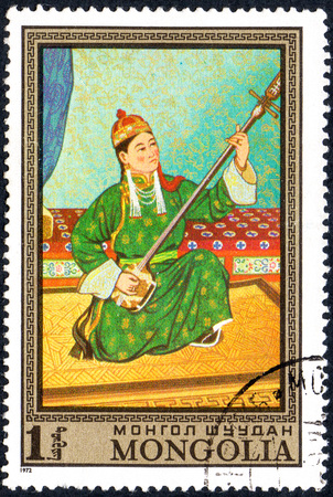 UKRAINE - CIRCA 2017: A postage stamp printed in Mongolia shows Young musician, girl playing on a stringed musical instrument, series Paintings by contemporary artists in Ulan Bator Museum, circa 1972
