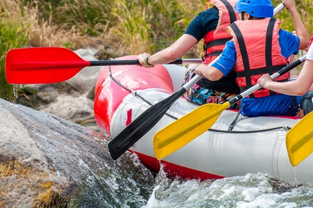 Rafting. Overcoming obstacles. Close-up view of oars with splashing water.