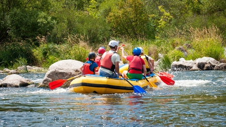 Rafting along the rough river rapids. Extreme vacation in nature.