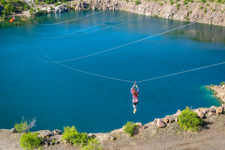 Zipline. The woman in the equipment slides on a steel cable. Trolley Track Over the lake. Extreme and active rest. Banque d'images