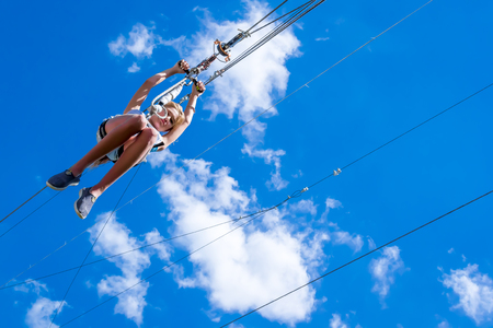 Ukraine, Migea - July 30, 2017: Zipline. A view of a blue sky with white clouds. Extreme and active rest.