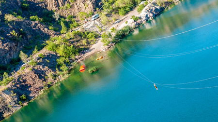 Zipline. Human in the equipment slides on a steel cable. Trolley Track Over the lake. Extreme and active rest. Stock Photo