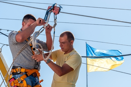 Ukraine, Migea - July 30, 2017: Zipline. The instructor conducts the instruction on the safety of the next fan of an extreme. Starting platform on a high rock. Extreme and active rest.