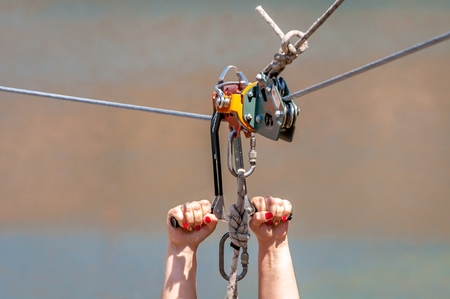 Zipline. Equipment for safe sliding on steel cable. Womans hands close-up during the flight. Banque d'images