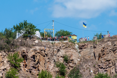 Ukraine, Migea - July 30, 2017: Zipline. Starting platform on a high rock. The man in the equipment slides on a steel cable. Trolley Track Over the lake. Extreme and active rest.