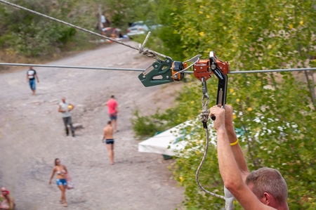 Ukraine, Migea - July 30, 2017: Zipline. Equipment for safe sliding on steel cable. Male hands close-up while flying. Impact Trolley - roller for high-speed zipline. Éditoriale