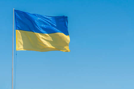 Yellow-blue flag of Ukraine in the wind against the blue sky. Banque d'images