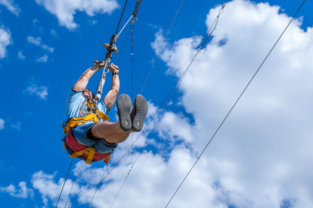 Ukraine, Migea - July 30, 2017: Zipline. A view of a man sliding on a steel cable against a beautiful blue sky with white clouds. Extreme and active rest. Éditoriale