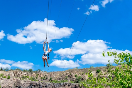 Ukraine, Migea - July 30, 2017: Zipline. A view of a child sliding on a steel cable against a beautiful blue sky with white clouds. Extreme and active rest.