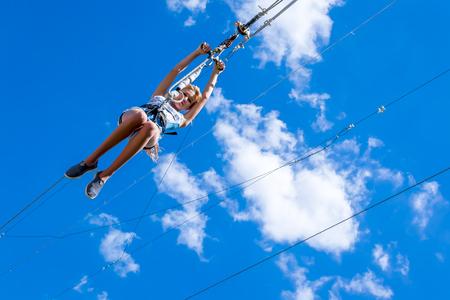 Oekraïne, Migea - 30 juli 2017: Zipline. Een weergave van een kind dat op een stalen kabel glijdt tegen een mooie blauwe lucht met witte wolken. Extreme en actieve rust.