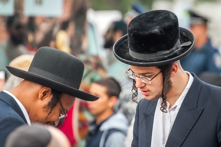 Uman, Ukraine - 2 October 2016: Rosh Hashanah, Jewish New Year 5777. It is celebrated at the grave of Rabbi Nachman. Pilgrims in traditional festive clothes. Conversation between two Hasidic Jews.