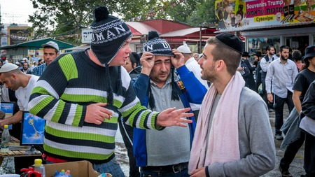 Uman, Ukraine - 2 octobre 2016: Rosh Hashanah, nouvelle année juive 5777. Les pèlerins de Hasidim en tenue festive traditionnelle célèbrent la messe sur l'Uman. Vendeurs de souvenirs. Banque d'images - 84306496