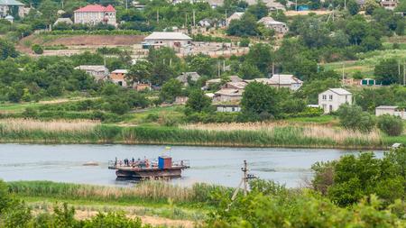 Ukraine, Southern Bug River - 18 juin 2017: traversée en ferry. Le ferry se déplace avec l'aide de la force musculaire d'un homme. Reforme le câble en acier. Un tel ferry est unique en Ukraine. Banque d'images - 84598261